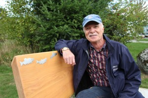 Mark Angelo sits on a bench dedicated to his efforts at BCIT beside Guichon Creek. Credit: BCIT.