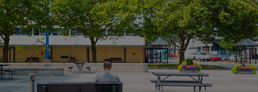 campus life feature image - guy sitting on a bench alone at bcit court yard